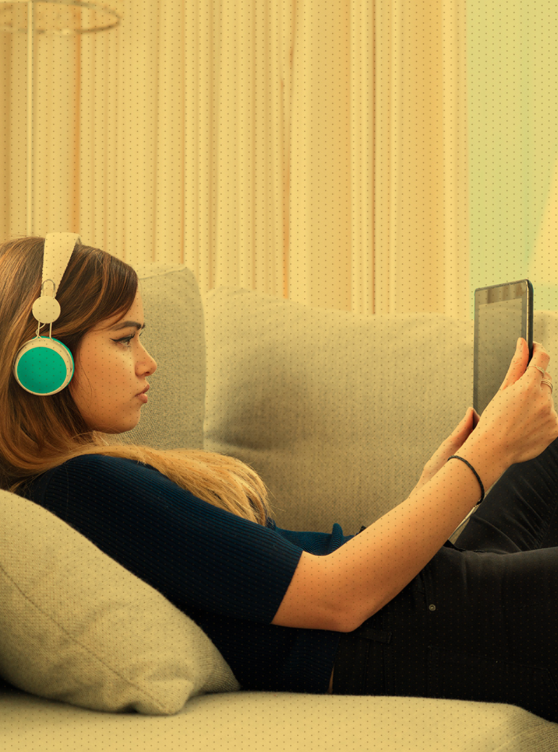 Women on couch wearing headphones looking at tablet