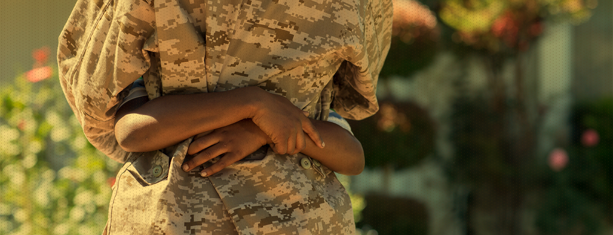 Adult in camouflage hugging child